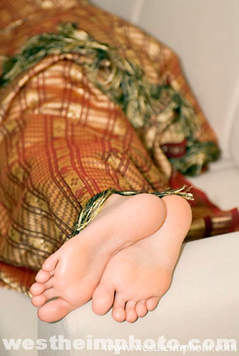 Close Up Of A Girls Feet Sticking Out From Under Blanket Relaing On